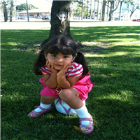 Girl in a pink outfit sitting on a soccer ball