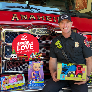 Firefighter with toys in front of a fire engine.